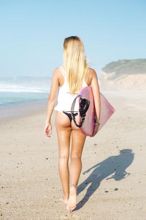 teen girl bikini: A beautiful surfer girl walking at the beach with her surfboard