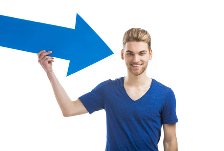 choose person: Good looking young man holding a blue arrow, isolated on a white background