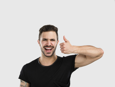 cool boys: Studio portrait of a funny young man smiling and with thumsb up