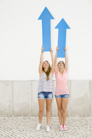 happy teenagers: Beautiful and happy teenagers pointing blue arrows to the sky
