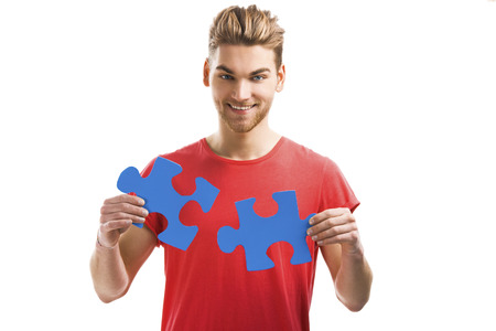 dovetail: Good looking young man holding a blue puzzle piece, isolated on a white background