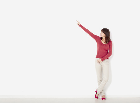 overloading: Beautiful young woman  against to a white wall pointing to the right side with copyspace