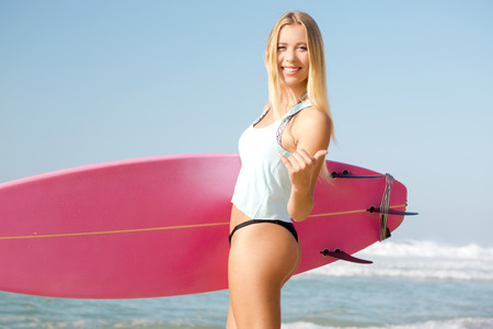 pink bikini: A beautiful surfer girl looking at the camera with her surfboard