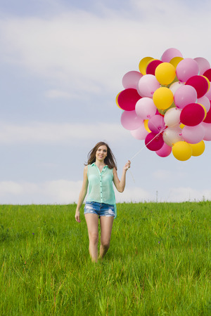 Young beautiful woman having fun with balloons on a green meadow photo