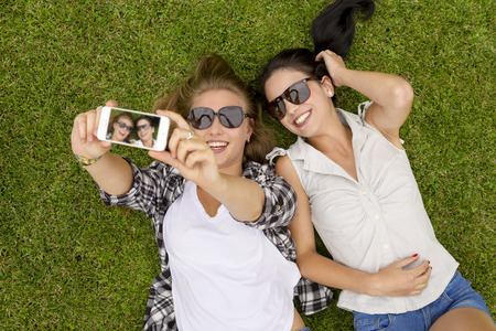 friends laughing: Female best friends lying on the grass and taking selfies