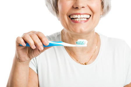 Portrait of a happy old woman brushing her teeth Stock Photo