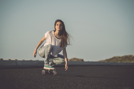 longboard: Young woman making downhill with a skateboard