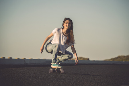 skate board: Young woman making downhill with a skateboard