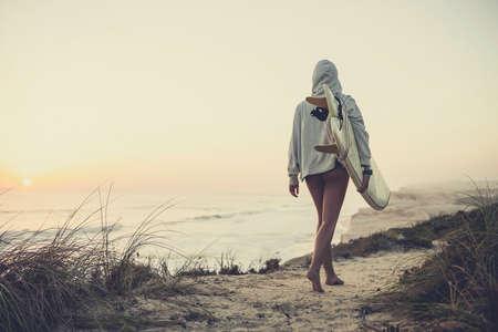 Belle femme à la recherche de Surfer les vagues Banque d'images