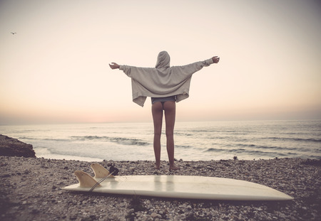 mediate: Beautiful female Surfer looking for the waves