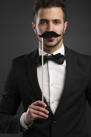 mr: Handsome young man holding a fake mustache