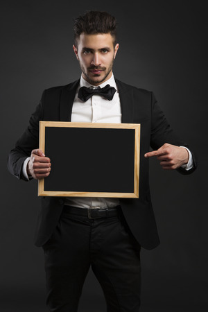 Studio portrait of a handsome young man holding a chalkboard photo