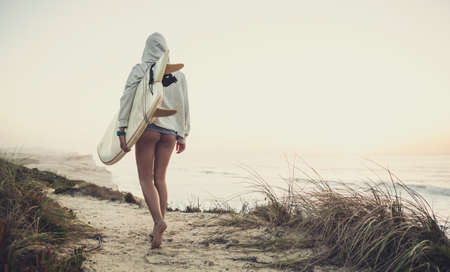 walk board: Beautiful female Surfer looking for the waves