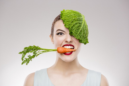 eating up: Beautiful woman with a carrot on the mouth