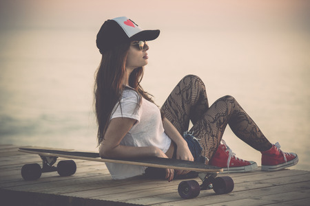 Beautiful fashion skater girl posing with  a skate board photo