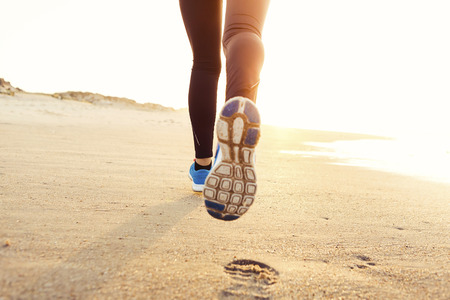 Schöne und gesunde Frau am Strand laufen