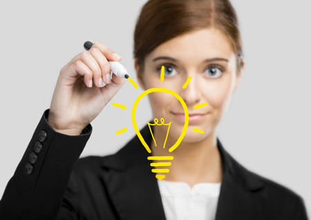 lady with the lamp: Beautiful woman drawing a lamp on a glass board Stock Photo