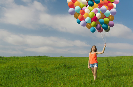 fluctuate: Young beautiful woman having fun with balloons on a green meadow