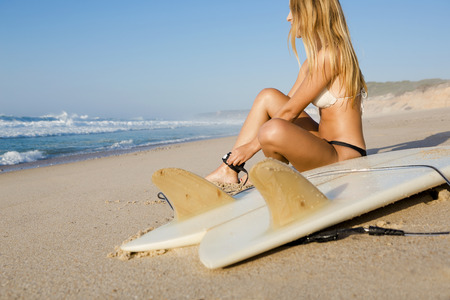 surfboard fin: Beautiful woman on the beach getting ready for surf