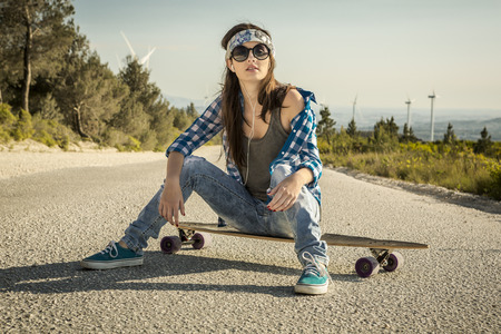swag: Beautiful young woman sitting over a skateboard