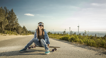 young woman sitting: Beautiful young woman sitting over a skateboard