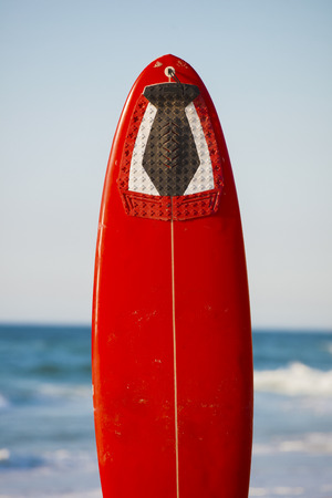 Red surfboard on the sand on a very beautiful sunny day Stock Photo