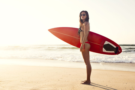 surfboard: A beuatiful and sexy surfer girl at the beach with her surfboard Stock Photo