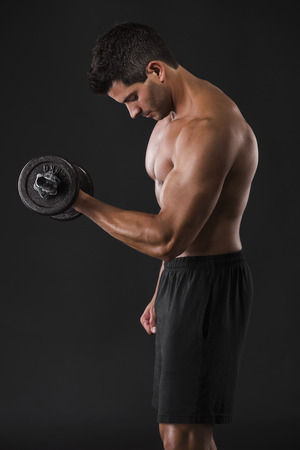 Portrait of a muscular man lifting weights against a dark background Stock Photo