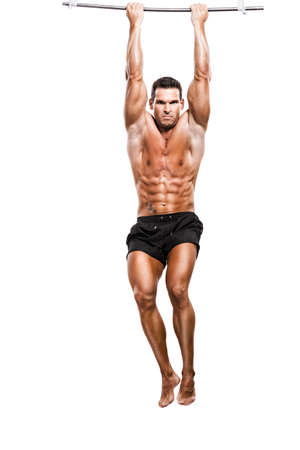 full suspended: Muscle man in studio making elevations, isolated over a white background