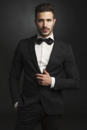 Ritratto di un bellissimo uomo latino sorridente che indossa un tuxedo