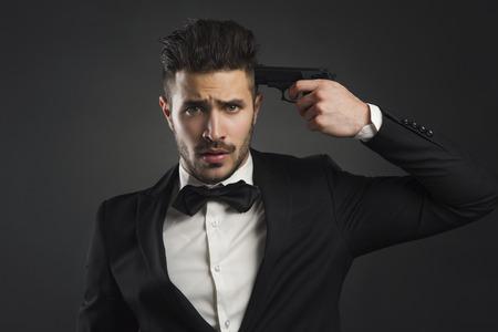 Stressed businessman giving a gunshot on his own head