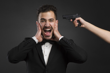 man yelling: Man yelling with a weapon pointing on his head