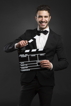 film director: Portrait of a beautiful latin man with tuxedo and holding a clapboard