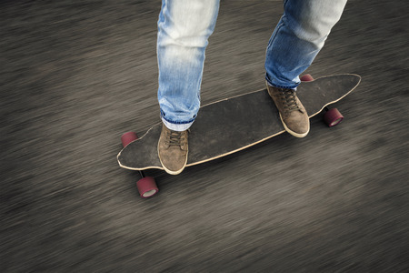 longboard: Detail of a young man feet riding a skateboard Stock Photo