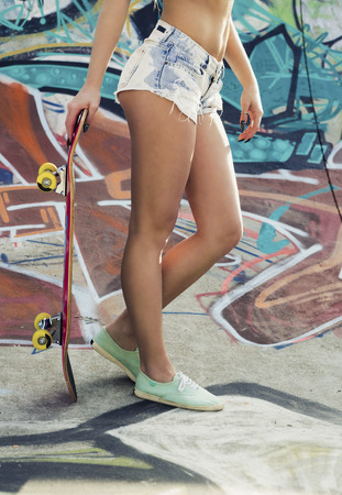 board shorts: Beautiful and sexy street girl with her skateboard