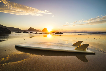 surfboard fin: Silhouette of a surfboard at the beach with reflection Stock Photo