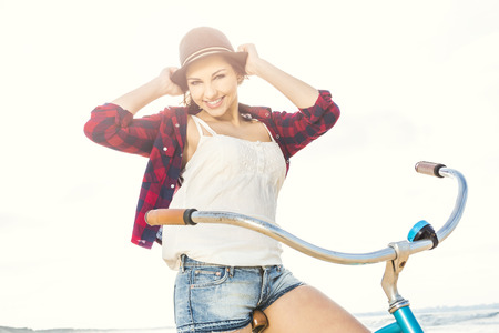 An attractive young woman riding her bicycle on the beach photo