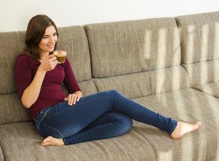 capuchino: Beautiful woman at home drinking a capuchino