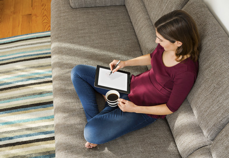 confortable: Beautiful woman at home in the sofa and working with a tablet Stock Photo