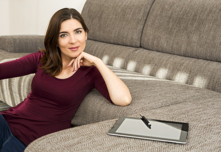 working at home: Gorgeous woman at home working with a tablet