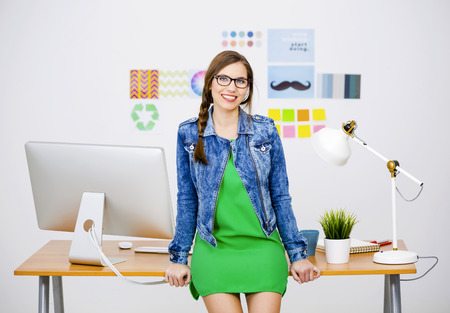 freelancer: Woman working at desk In a creative office, breaking time Stock Photo