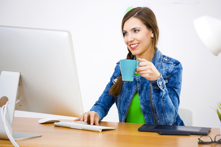 home offices: Woman working at desk In a creative office holding a cup