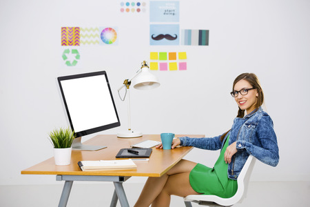 freelancer: Woman working at desk In a creative office, using a computer Stock Photo