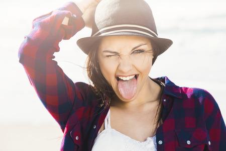 lengua afuera: Portrtait de una niña feliz disfrutando el día en la playa Foto de archivo