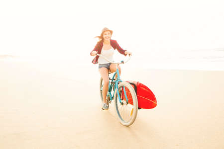 free riding: Surfer young woman riding her bicycle on the beach