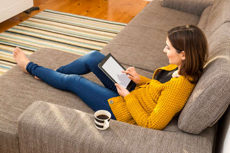 confortable: Beautiful woman working at home with a tablet and drinking coffee