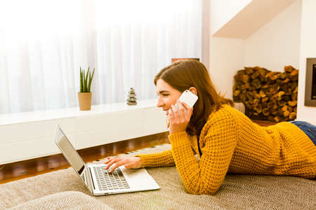 confortable: Beautiful woman at home working with a laptop and making a phone call