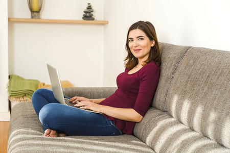 home confort: Beautiful woman working from the confort of home with her laptop