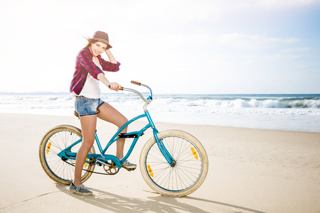 free riding: Beautiful young woman riding her bicycle at the beach
