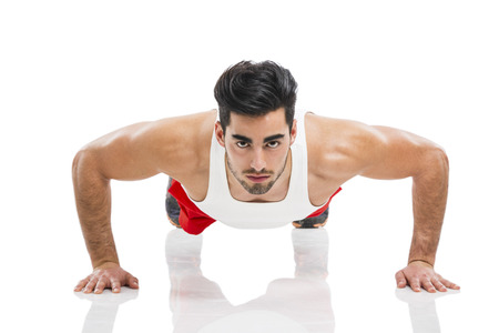 the athlete: Athletic young man making push-up, isolated over a white background